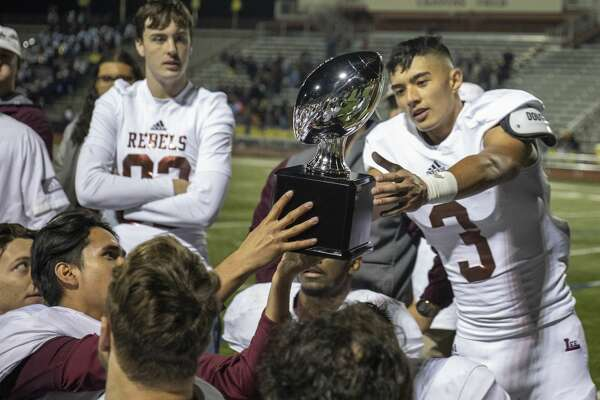 Lee's Karl Taylor (3) is passed the trophy after Coach Hartman acknowledged his break up play in the fourth quarter which gave Lee back the ball Saturday, Nov. 23, 2019 at Cravens Stadium in Arlington.