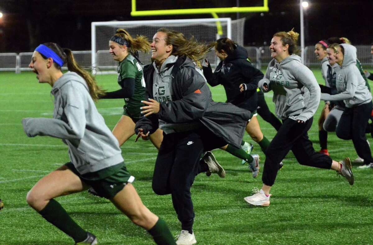 Guilford team members rush onto the field to celebrate after beating East Lyme during CIAC State Girls Soccer Tournament action in Hartford, Conn., on Saturday Nov. 23, 2019.