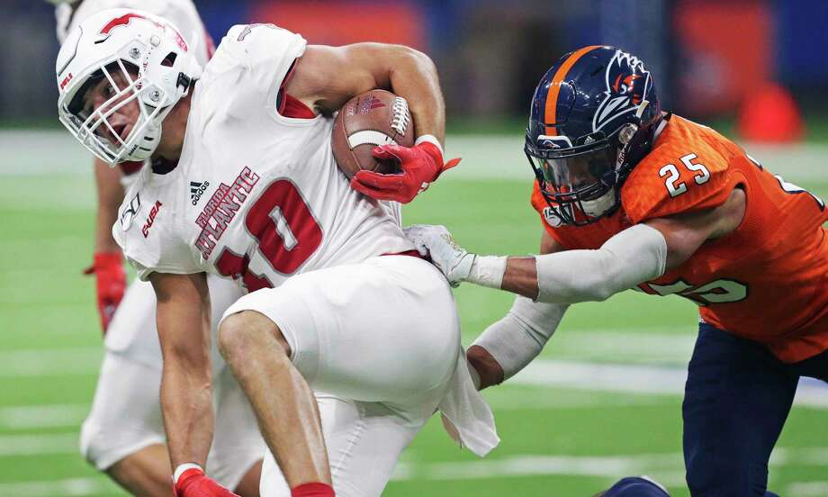 Owl receiver John Raine is chased around the left side by Roadrunner safety Carly Austin III as UTSA plays Florida Atlantic at the Alamodome on Nov. 23, 2019. Photo: Tom Reel, San Antonio Express-News / Staff Photographer / **MANDATORY CREDIT FOR PHOTOG AND  SAN ANTONIO EXPRESS-NEWS/NO SALES/MAGS OUT/TV