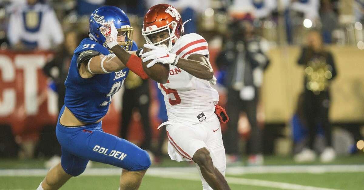 Tulsa defensive end Cullen Wick, left, tries to tackle Houston wide receiver Marquez Stevenson during an NCAA college football game Saturday, Nov. 23, 2019, in Tulsa, Okla. (Brett Rojo/Tulsa World via AP)