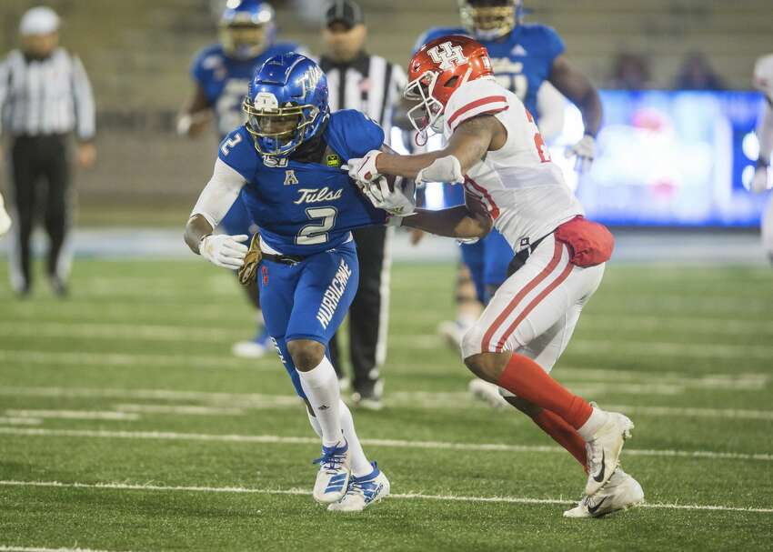 Tulsa wide receiver Keylon Stokes runs after a reception as Houston safety Jordan Moore tries to tackle him during an NCAA college football game Saturday, Nov. 23, 2019, in Tulsa, Okla. (Brett Rojo/Tulsa World via AP)