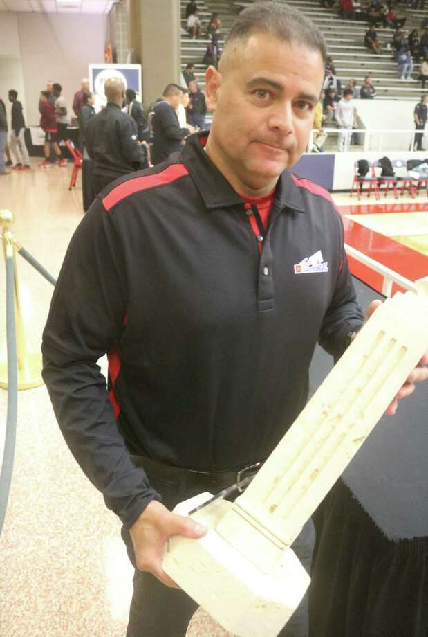 Pasadena ISD Athletic Director Rupert Jaso begins his trek to the Phillips Field House floor Saturday night, carrying the top trophy to the McDonald's Texas Invitational. Photo: Robert Avery