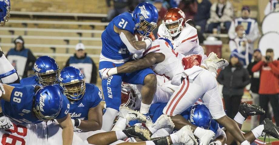 Tulsa running back T.K. Wilkerson is stopped short of the goal line by Houston linebacker Donavan Mutin during an NCAA college football game Saturday, Nov. 23, 2019, in Tulsa, Okla. (Brett Rojo/Tulsa World via AP) Photo: Brett Rojo/Associated Press