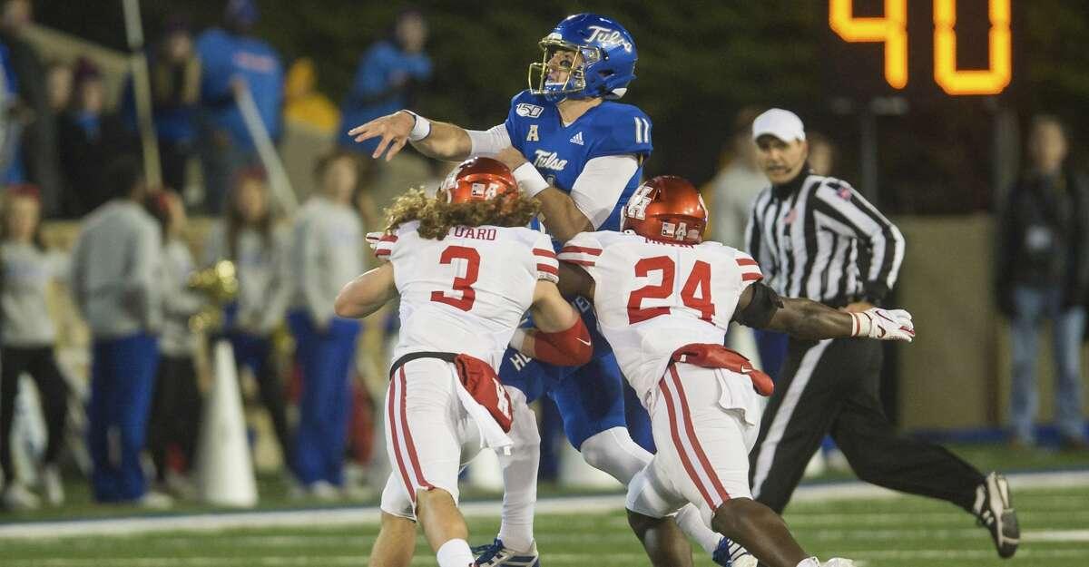 Tulsa quarterback Zach Smith, center, is hit by Houston safety Grant Stuard, left, and linebacker Donavan Mutin during an NCAA college football game Saturday, Nov. 23, 2019, in Tulsa, Okla. (Brett Rojo/Tulsa World via AP)