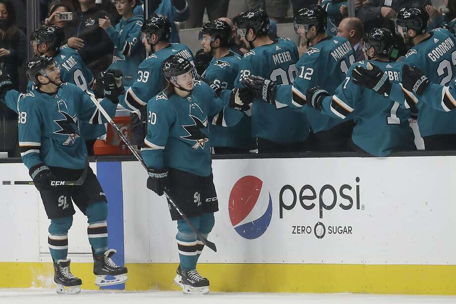 Sharks left wing Marcus Sorensen, foreground right, and defenseman Mario Ferraro skate past the bench to celebrate with teammates after Sorensen scored in the second period. Photo: Jeff Chiu / Associated Press