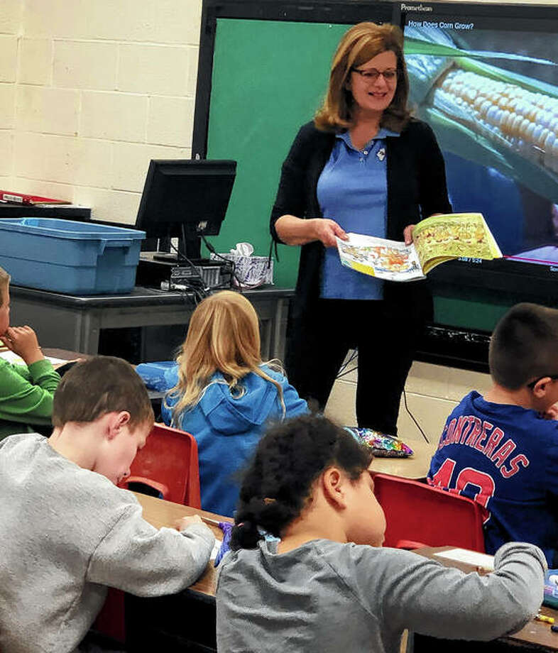 """Volunteer Lynn Curry reads the book """"Corn"""" by Gail Gibbons to third-graders at Griggsville-Perry Elementary School during the Pike-Scott Farm Bureau's Agriculture in the Classroom monthly lesson. Photo: Photo Provided"""