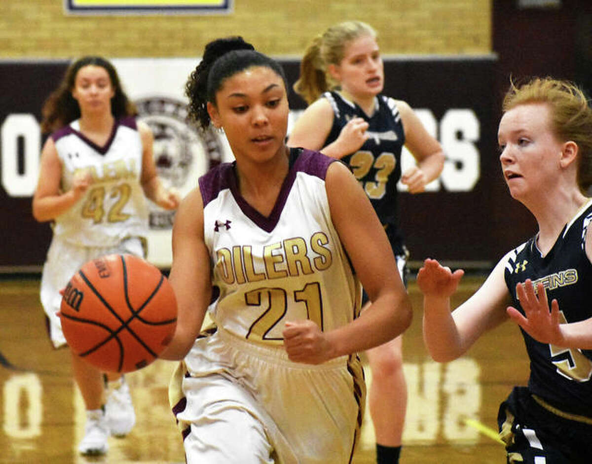 EA-WR's Adrianna Ulrich (21) drives on Father McGivney's Shannon Cadagin during the championship game of the Cat Classic girls basketball tournament Saturday in Dupo.