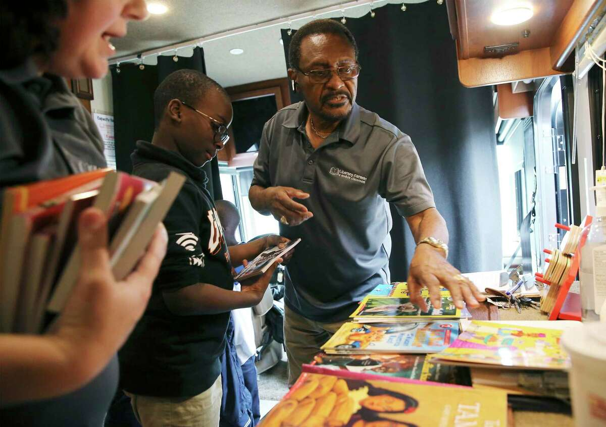 James Stewart (center) helps a school child pick out a book in the San Antonio Public Library Foundation's Literacy Caravan while visiting Camelot Elementary on Friday, Oct. 11, 2019. For the past 11 years the Army retiree has driven the Literacy Caravan, an RV filled with free books that is given out to children and their parents, to stops across San Antonio and South Texas.