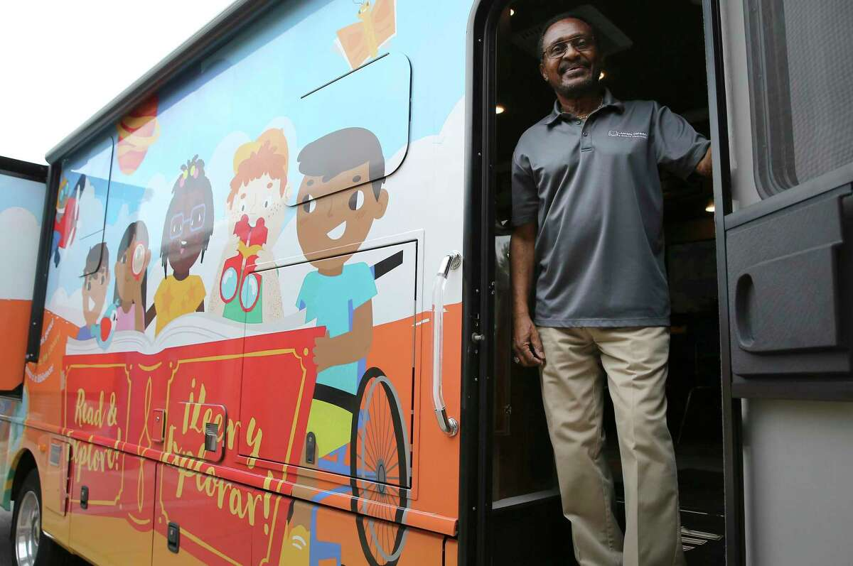 James Stewart stands at the entrance of the San Antonio Public Library Foundation's Literacy Caravanm ready to welcome kids at Camelot Elementary on Friday, Oct. 11, 2019. The San Antonio Public Library Foundation sponsors the caravan that reaches an estimated 10,000 parents and children annually in the Bexar County area. The latest iteration of the vehicle was donated by the Mays Family Foundation which provides more room and utility. There's also a wheelchair ramp for children with special needs.