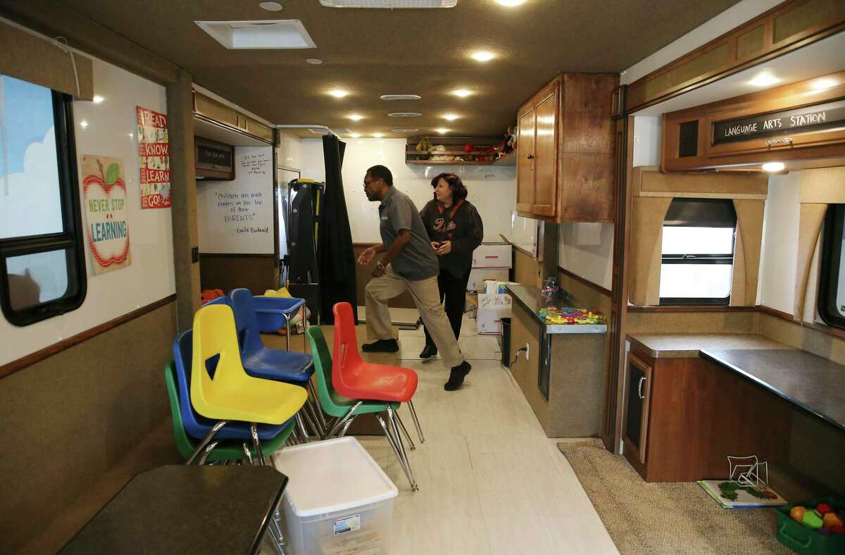 James Stewart (center) and Angela Bunting set up the interior of the Literacy Caravan before a visit by school children while visiting Camelot Elementary on Friday, Oct. 11, 2019. At each stop Stewart sets up the RV which is equipped with educational toys and activities. Students can play in the RV before they're handed a free book of their choice on the way out.