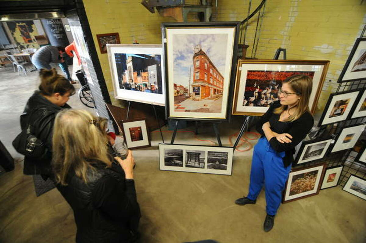 Photographer Jenna Carlie discusses her work with visitors at the inaugural Holiday Cheers Market in Alton on Saturday.