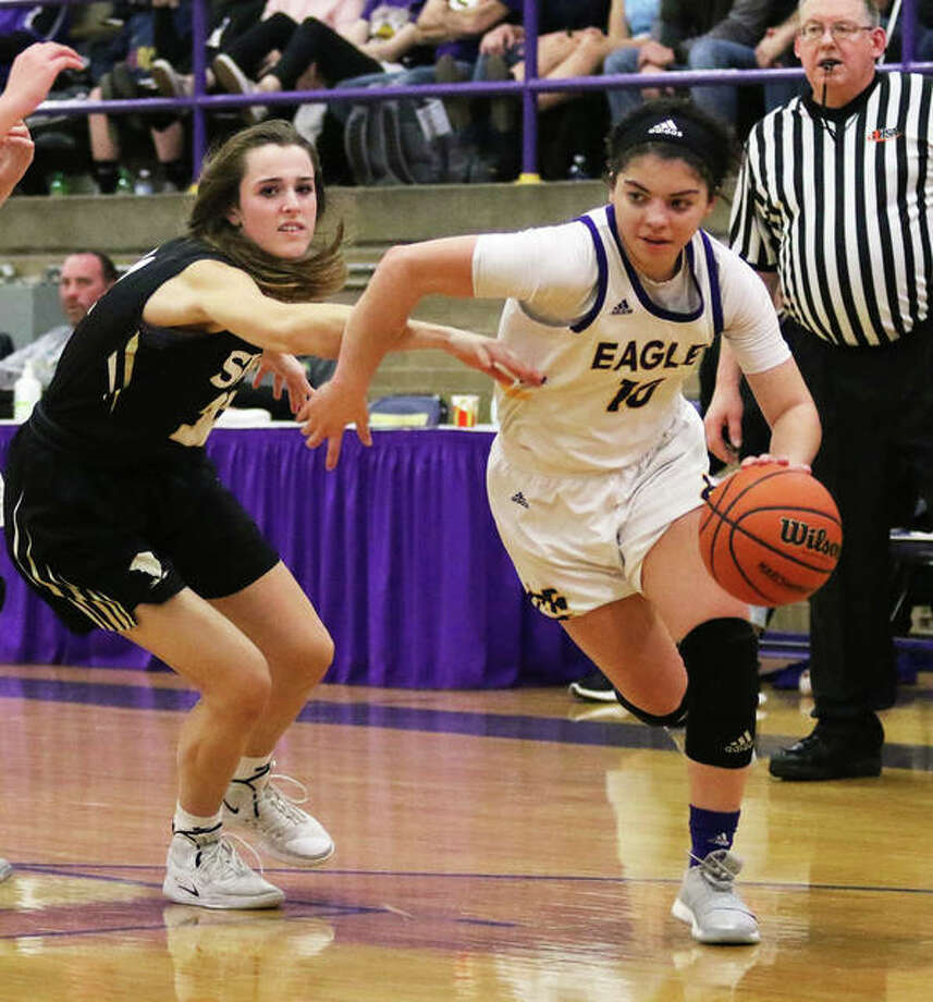 CM's Kourtland Tyus (right) drives past a Springfield SHG defender in last season's Class 3A sectional at Taylorville. Tyus and the Eagles were back in Taylorville on Friday and Saturday for three victories in the Taylorville Tourney. Photo: Greg Shashack / The Telegraph