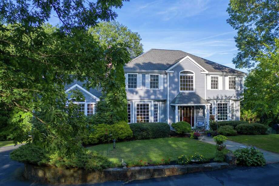 The gray colonial house at 129 Wedgewood Drive sits on a 5.42-acre property and invites indoor-outdoor living.