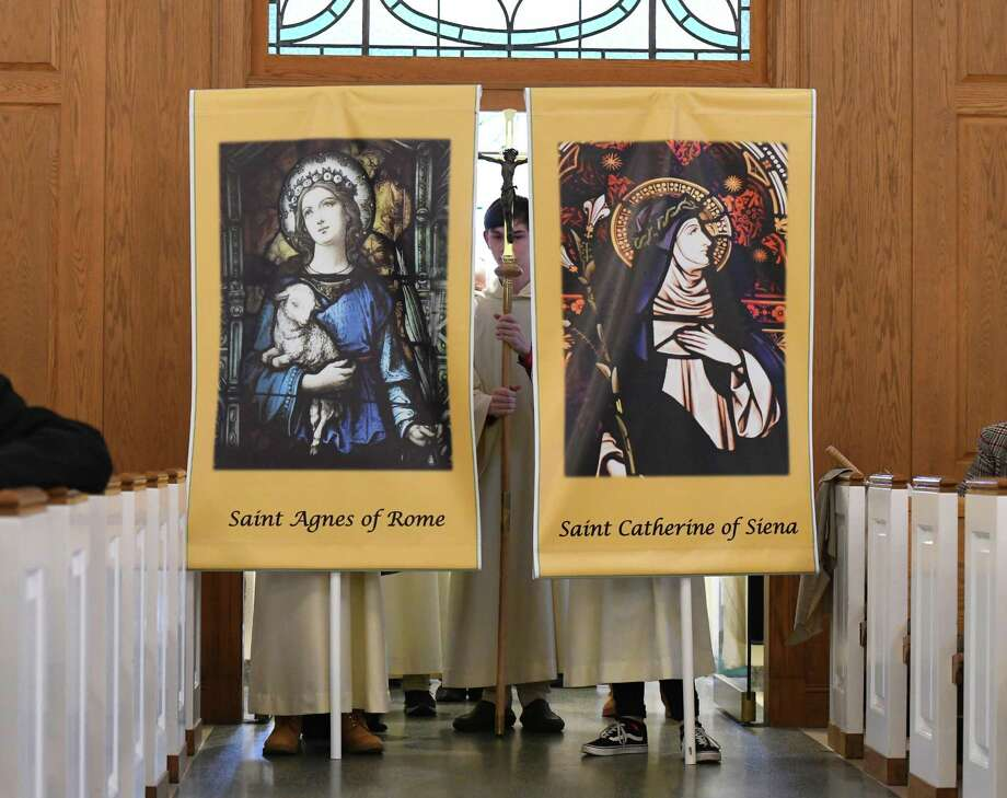 Mass begins with images of Saint Agnes of Rome and Saint Catherine of Siena after the merger of the two churchs at St. Catherine of Siena Church in the Riveride section of Greenwich, Conn. Sunday, Nov. 24, 2019. The new Parish of St. Catherine of Siena and St. Agnes celebrated the merger of the two churches with a procession in the rain from St. Agnes on Stanwich Road to St. Catherine on Riverside. Bishop of the Diocese of Bridgeport Frank Caggiano joined the end of the procession and led the 10:30 a.m. Mass at St. Catherine. Photo: Tyler Sizemore / Hearst Connecticut Media / Greenwich Time