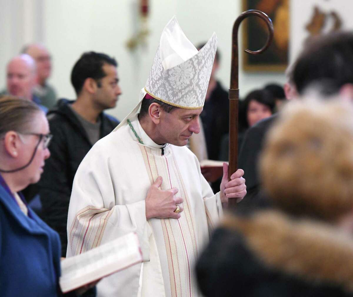 Bishop of the Diocese of Bridgeport Frank Caggiano enters Mass at St. Catherine of Siena Church in the Riveride section of Greenwich, Conn. Sunday, Nov. 24, 2019. He announced on Monday that parishes in his diocese will start saying public, outdoor Masses next Thursday. Some parishes will continue live-streaming the Mass, but will deliver Communion to the faithful who wait in their cars, while others will offer public Masses in their parking lots or with parishioners seated outside, socially distanced.