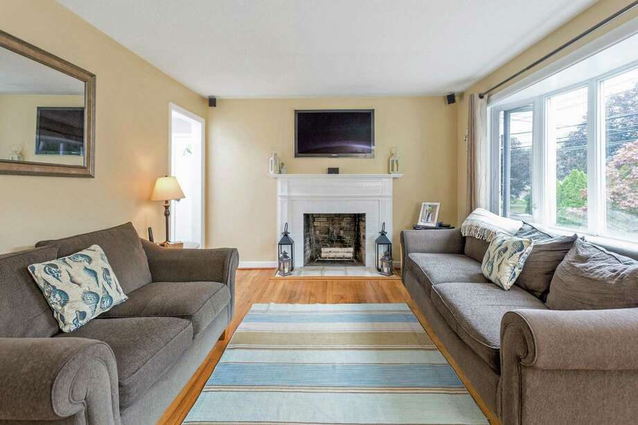 The living room has a fireplace and bow window.