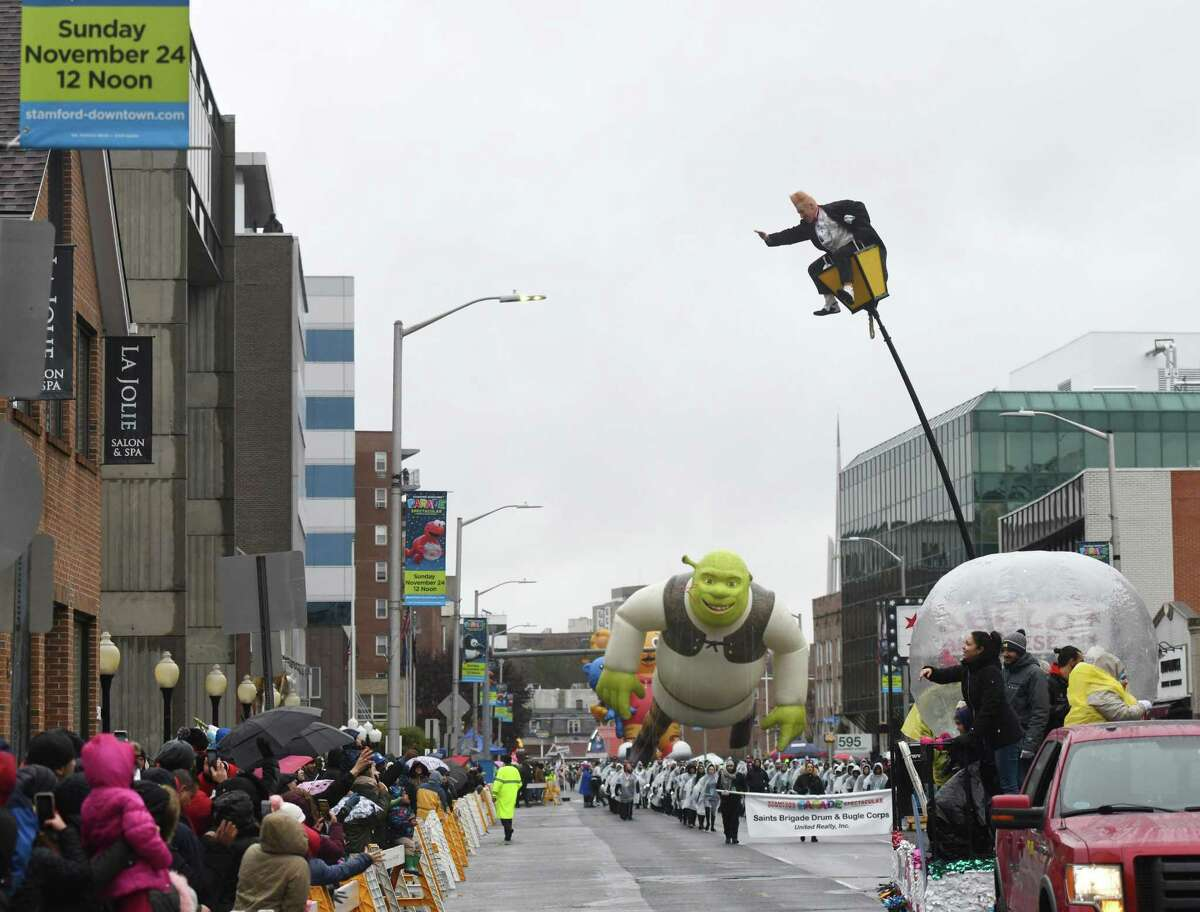 Circus performer Bello Nock keeps his balance and waves to the crowd while sitting high in a perch in front of a large Shrek balloon during the Stamford Downtown Parade Spectacular in Stamford, Conn. Sunday, Nov. 24, 2019. The parade, sponsored by the Stamford Advocate, featured many enormous helium balloons of popular characters including Clifford, Shrek, Bob the Builder, Peppa Pig and more. In between balloons, many musical and dance performances entertained guests bearing through the cold and windy weather.