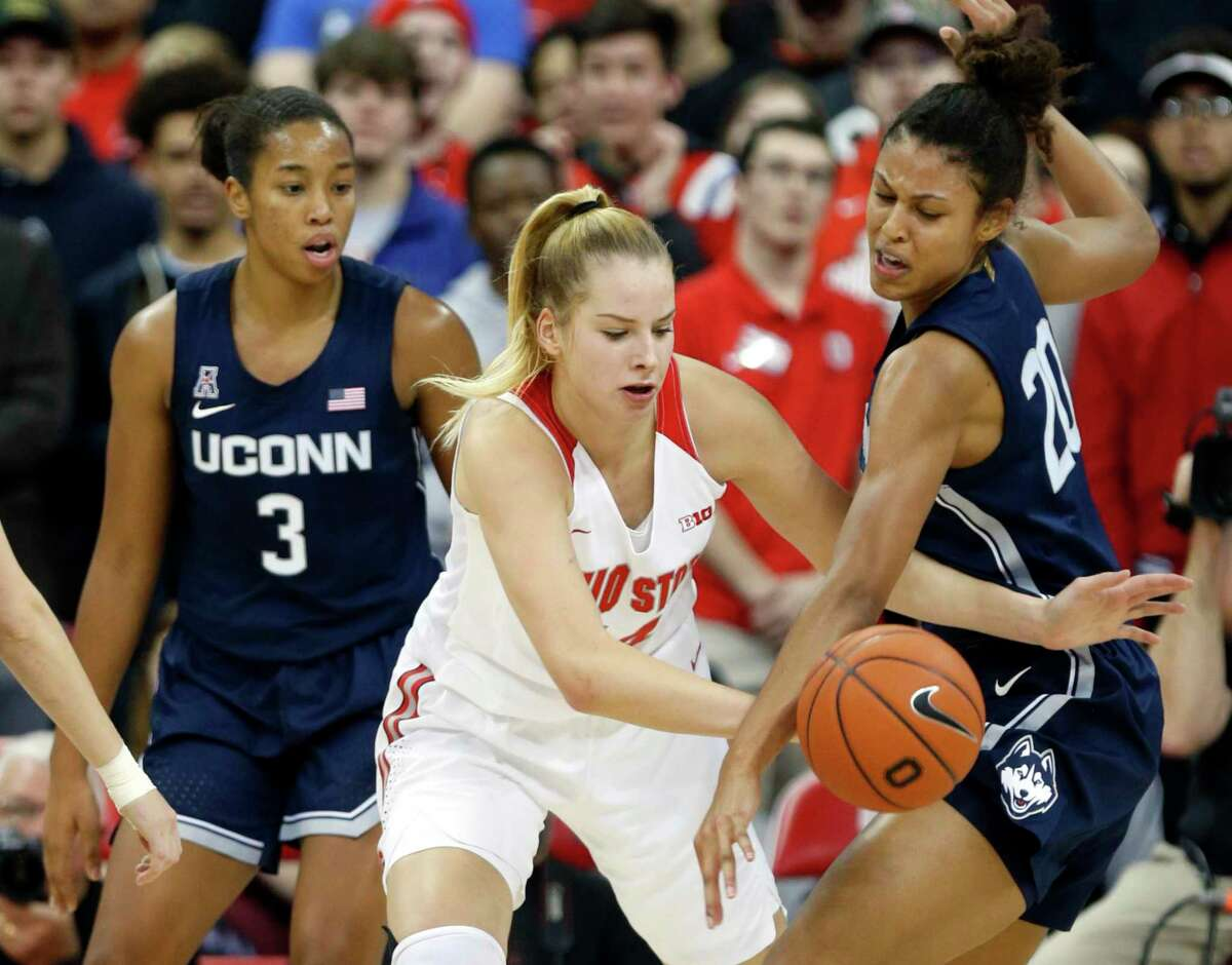 Ohio State forward Dorka Juhasz, center, works for the ball between Connecticut forwards Megan Walker, left, and Olivia Nelson-Ododa during an NCAA Women's basketball game in Columbus, Ohio, Sunday, Nov. 24, 2019.
