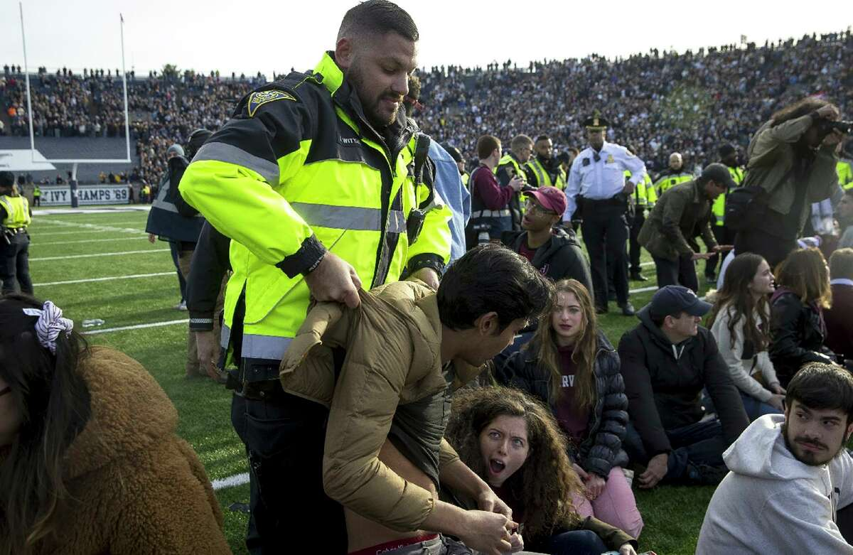 In this Saturday, Nov. 23, 2019, photo, an officer lifts a student up during a protest during halftime of the NCAA college football game between Harvard and Yale at the Yale Bowl in New Haven, Conn. Officials say 42 people were charged with disorderly conduct after the protest interrupted the game. (Nic Antaya/The Boston Globe via AP)