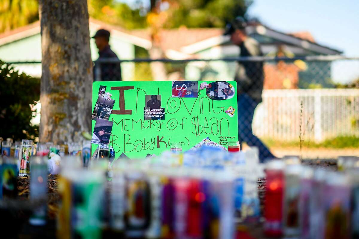 People pass a memorial for two boys, age 11 and 14, killed in the Searles Elementary School parking lot in Union City, Calif., on Sunday. Nov. 24, 2019.