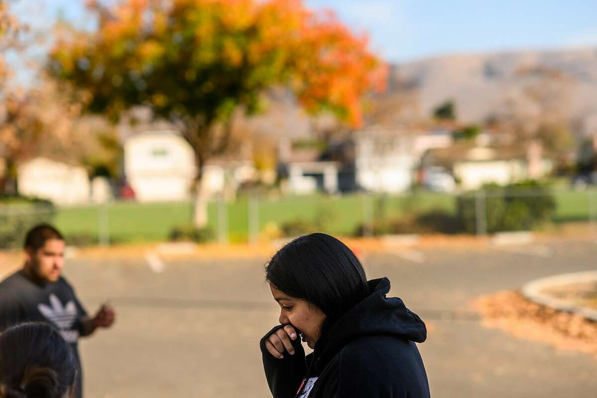 A woman, who declined to give her name, remembers a shooting victim at a makeshift memorial outside Searles Elementary School on Sunday, Nov. 24, 2019, in Union City, Calif. Authorities are searching for suspects in the fatal shooting of two boys, age 11 and 14, early Saturday morning.