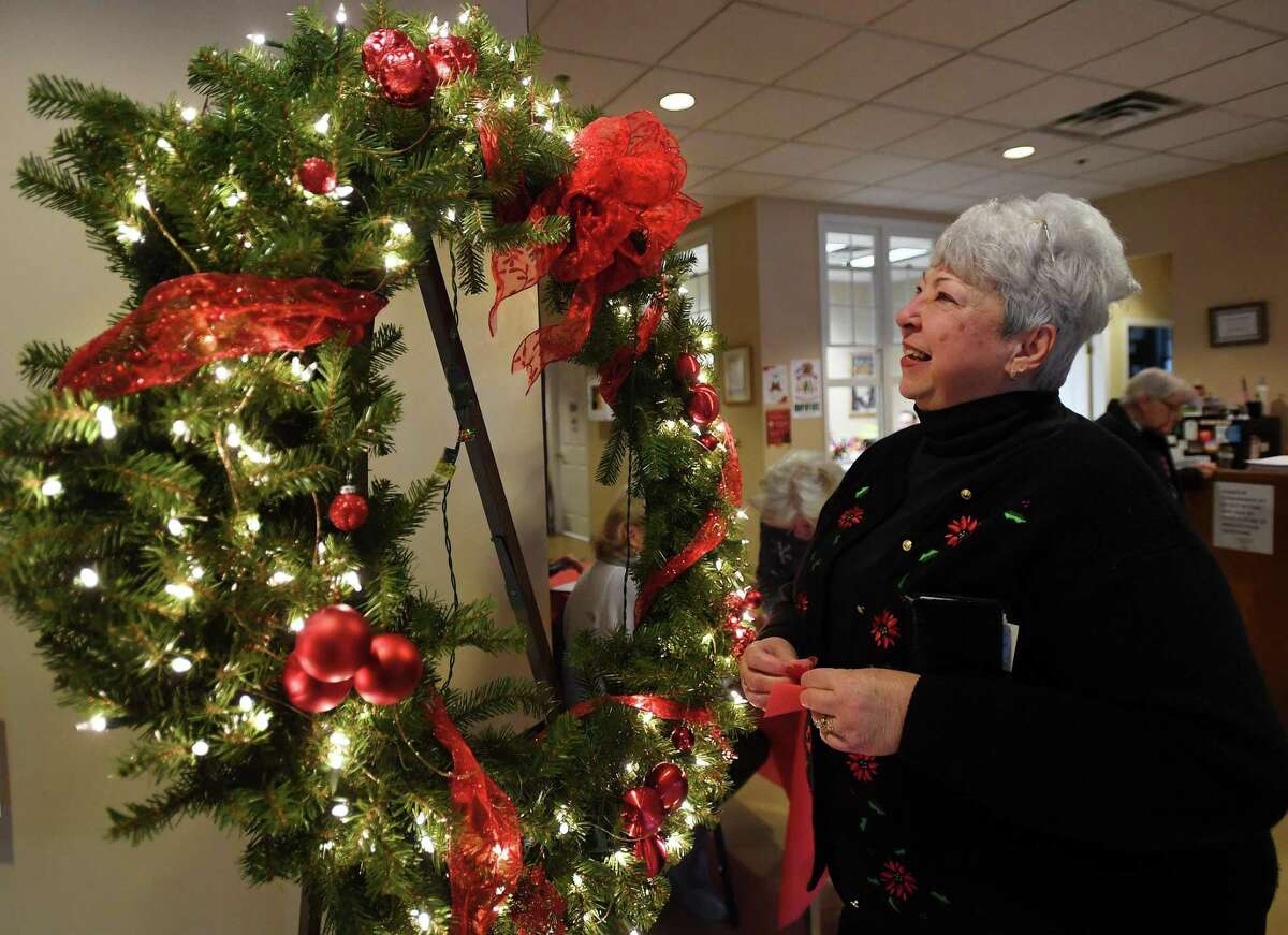 Nancy Valentine, of Ansonia, puts in tickets for the raffle of a large holiday wreath at the second annual Festival of Trees event at the Shelton Senior Center in Shelton on Sunday.