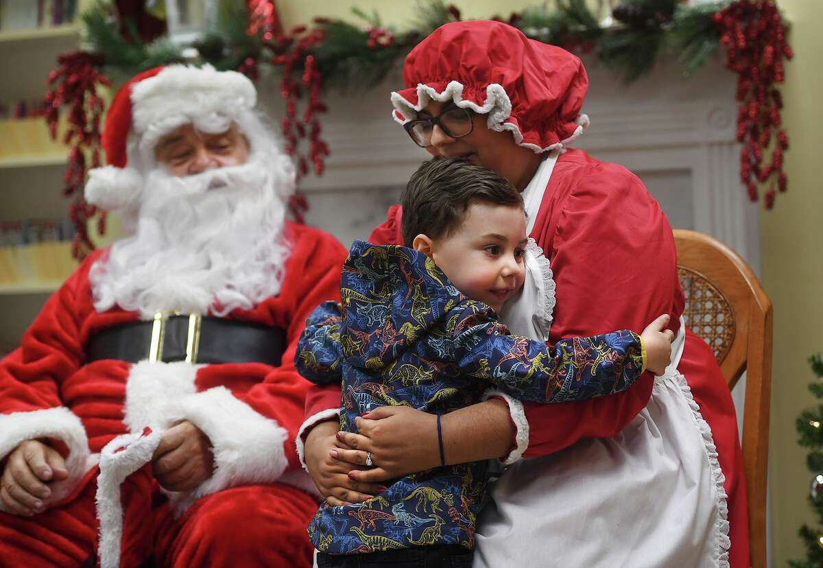 Sam Telesco, 4, of Seymour, has big hugs for Santa and Mrs. Claus at the event on Sunday.
