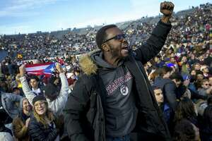 Harvard and Yale students protest during halftime of the NCAA college football game between Harvard and Yale at the Yale Bowl in New Haven on Saturday. Officials say 42 people were charged with disorderly conduct after the protest interrupted the game.