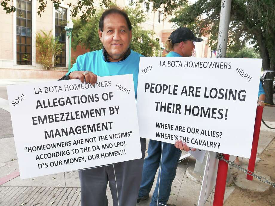 La Bota Homeowners Voices United (HVU) spokesperson Memo Castro holds some of the signs group members used while protesting Nov. 5 outside the Webb County Justice Center where some homes from La Bota were up for auction. Photo: Cuate Santos /Laredo Morning Times / Laredo Morning Times