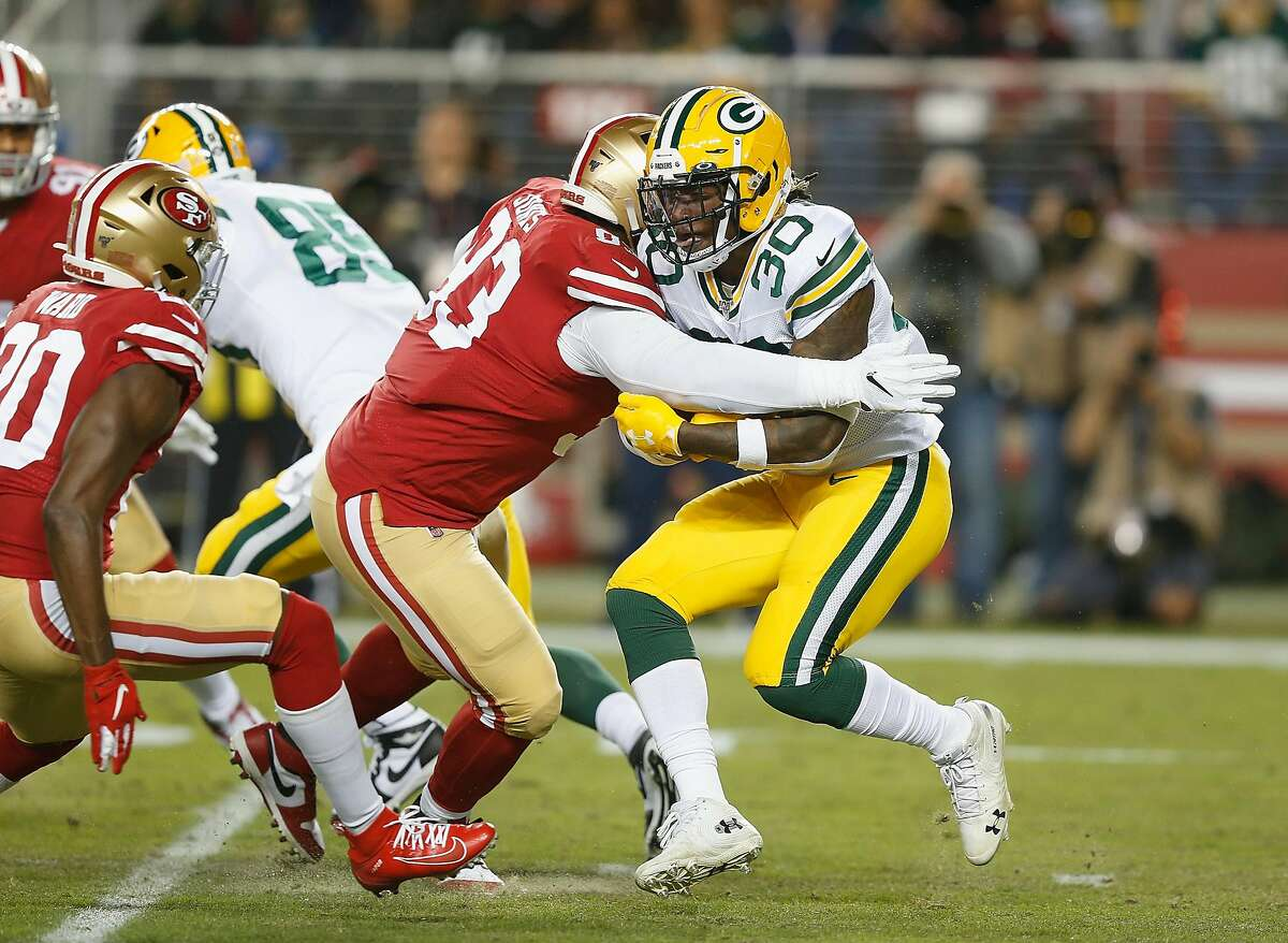 SANTA CLARA, CALIFORNIA - NOVEMBER 24: Aaron Jones #33 of the Green Bay Packers is tackled by D.J. Jones #93 of the San Francisco 49ers behind the line of scrimmage in the first quarter at Levi's Stadium on November 24, 2019 in Santa Clara, California. (Photo by Lachlan Cunningham/Getty Images)