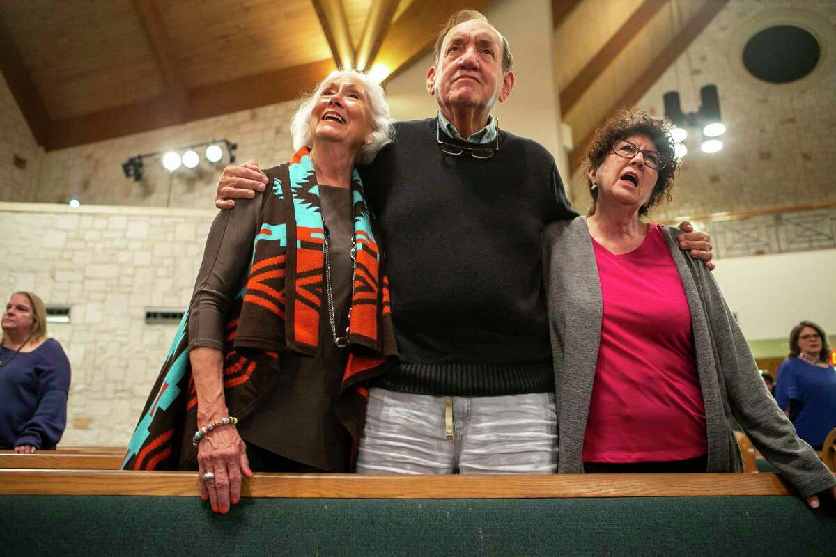 Susan Jones, from left, Ross Jones and Debbie K. Linck, all of San Antonio, wrap their arms around each other during the benediction of the third annual Interfaith Thanksgiving service at University United Methodist Church in San Antonio on Sunday.