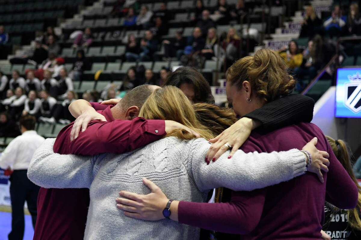 Burnt Hills volleyball coaches and team staff embrace following the team's win in the Class A State Championship against West Irondequoit on Sunday, Nov. 24, 2019, at Cool Insuring Arena in Glens Falls, N.Y. (Jenn March, Special to the Times Union)