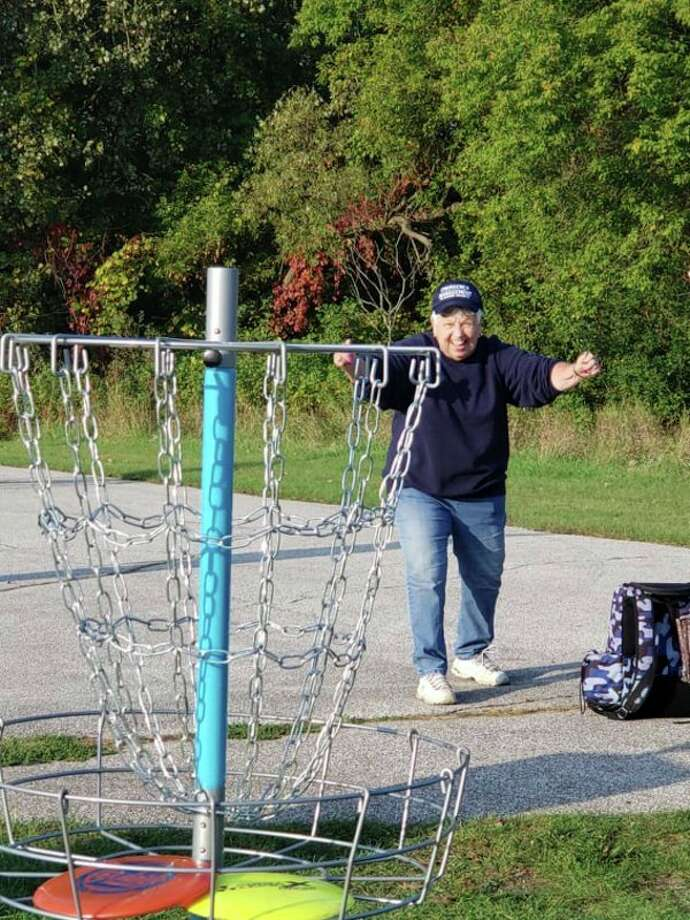 Gladwin Mayor Dee Jungman plays disc golf last month during a walk-through on the proposed nine-hole course in the city's North Park. Jungman and other city officials are supportive of bringing the sport to the city. (Photo provided)