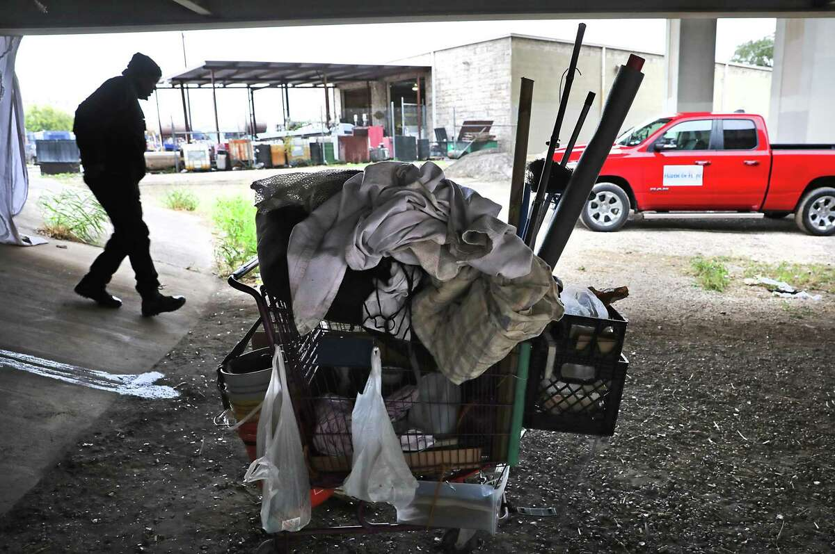 Ron Brown, Haven for Hope outreach director, walks past a homeless man's cart of belongins after Brown gave him a blanket as Brown and city officials made the rounds in the downtown area in late October.