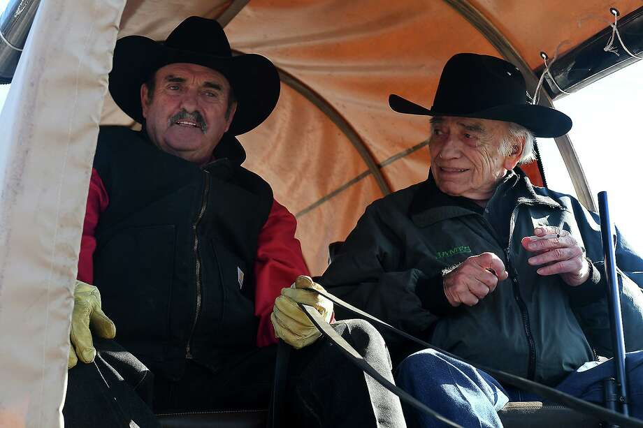 "Parade Grand Marshall James Drury (""The Virginian""), right, rides in a covered wagon driven by Jim Blount of the Sam Houston Trailriders as they move down Main Street during the 54th Annual Tomball Holiday Parade on Nov. 23, 2019. Photo: Jerry Baker, Houston Chronicle / Contributor / Houston Chronicle"