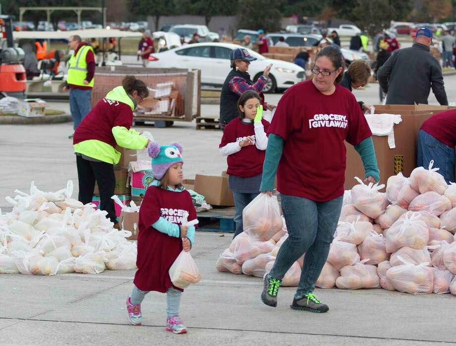 Kinsley Eudy, 4, carries a bag of oranges alongside her mother, Becca, during The Ark Church's annual grocery giveaway. Photo: Jason Fochtman, Houston Chronicle / Staff Photographer / Houston Chronicle