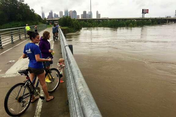 People take advantage of a lull in the rains from Tropical Storm Harvey to check out White Oak Bayou from a bike path in the Heights. (Jill Karnicki / Houston Chronicle)
