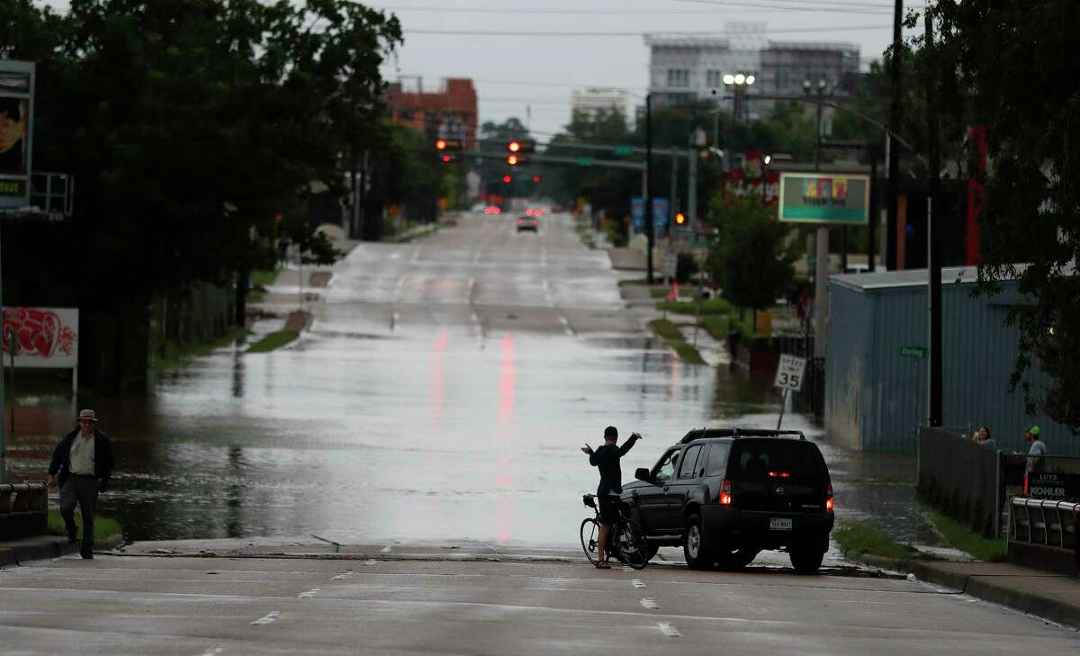 A bicyclist chats with a motorist on the Durham Bridge with water from the White Oak Bayou covering it after heavy rain from Hurricane Harvey fell overnight, Sunday, Aug. 27, 2017, in Houston. ( Karen Warren / Houston Chronicle )