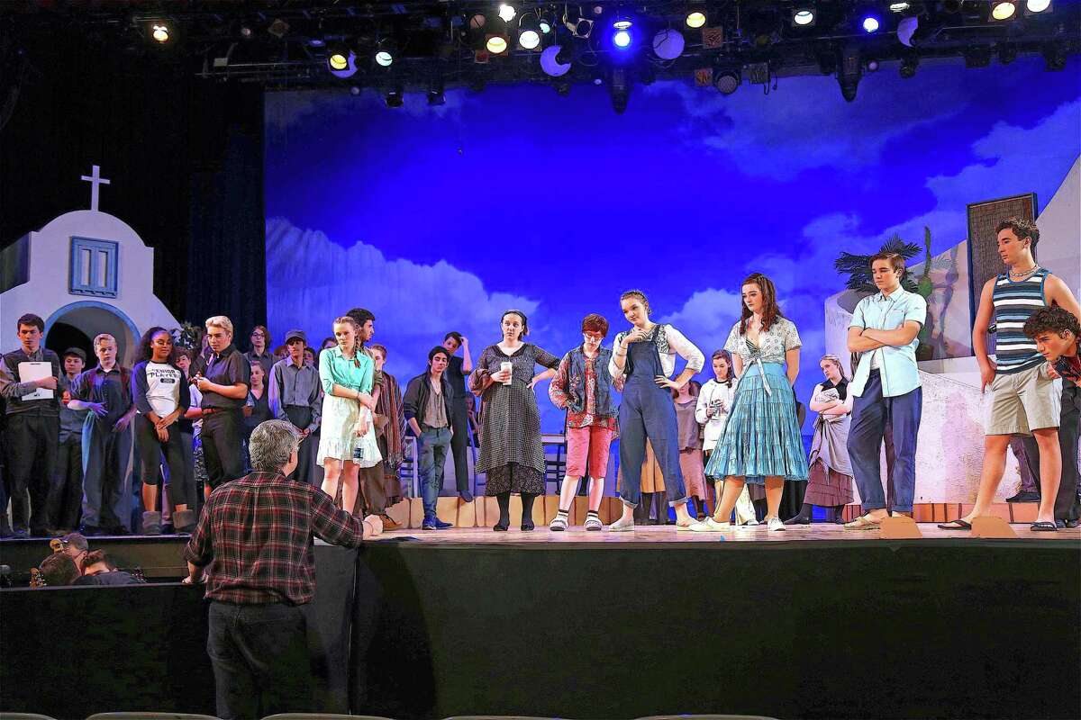 Actors listen to Don Rickenback, musical director, give instructions at the performance of