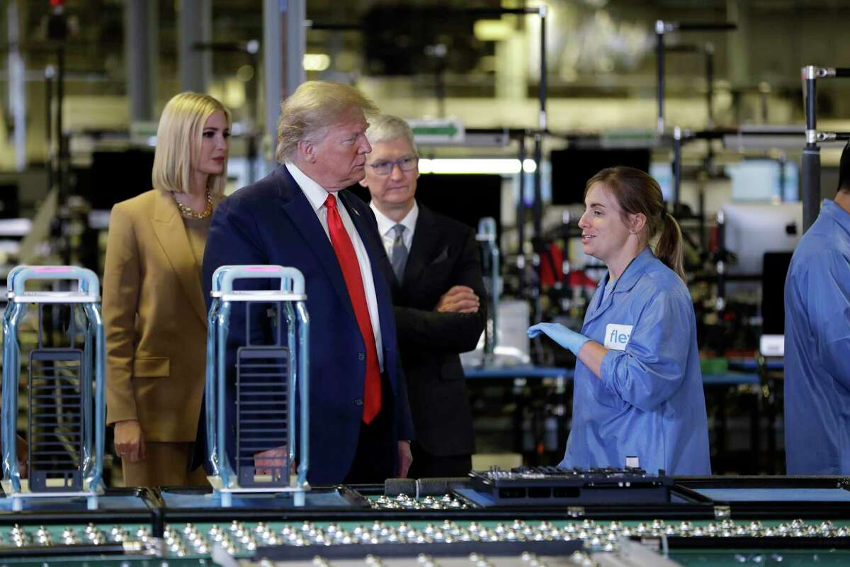 President Donald Trump speaks during a tour of an Apple manufacturing plant, Wednesday, Nov. 20, 2019, in Austin, as Rep. John Carter, R-Texas, left, looks on. (AP Photo/ Evan Vucci)