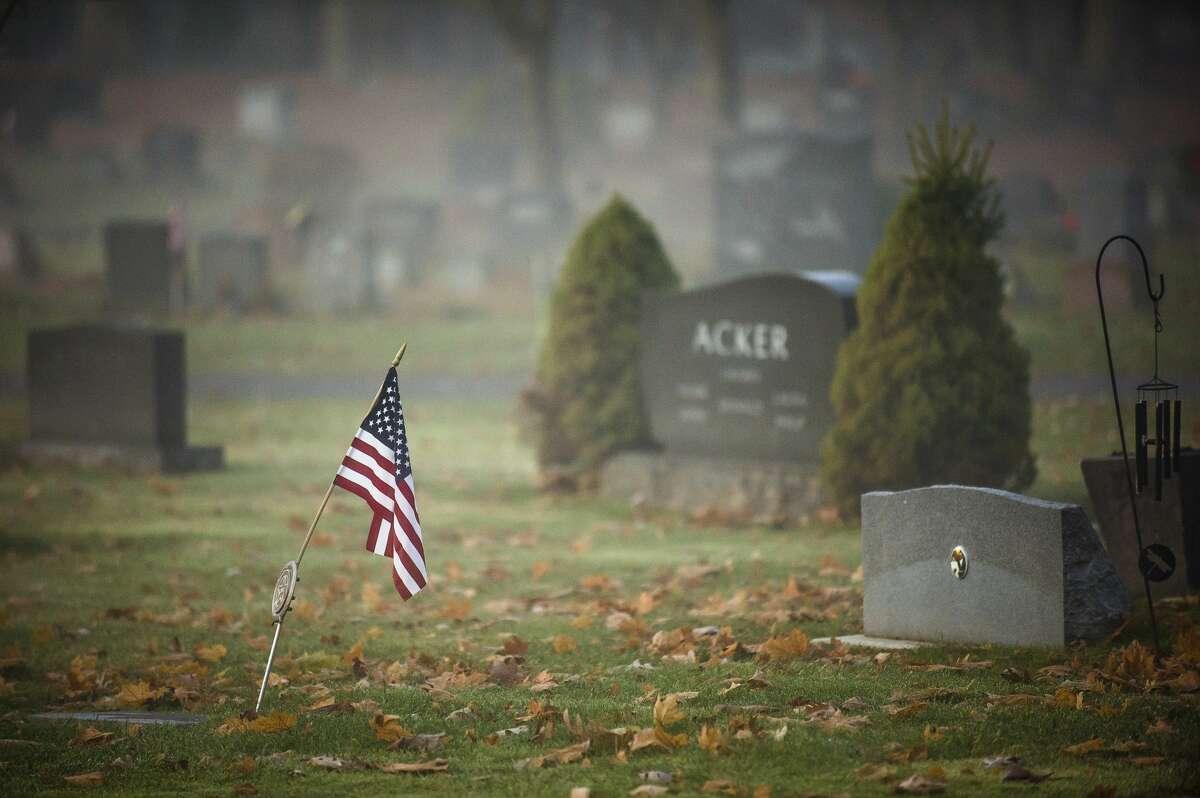 An American flag is shown on a gravesite at Midland Cemetery in 2019. (Katy Kildee/kkildee@mdn.net)
