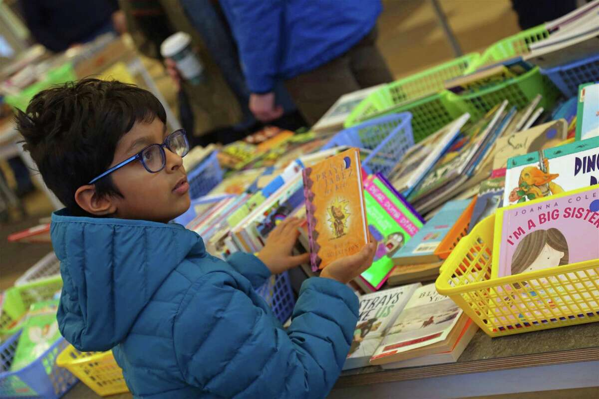 Hasan Nasar, 8, of Westport, looks through the children's section at the Holiday Book Sale at The Westport Library on Nov. 24, 2019, in Westport.