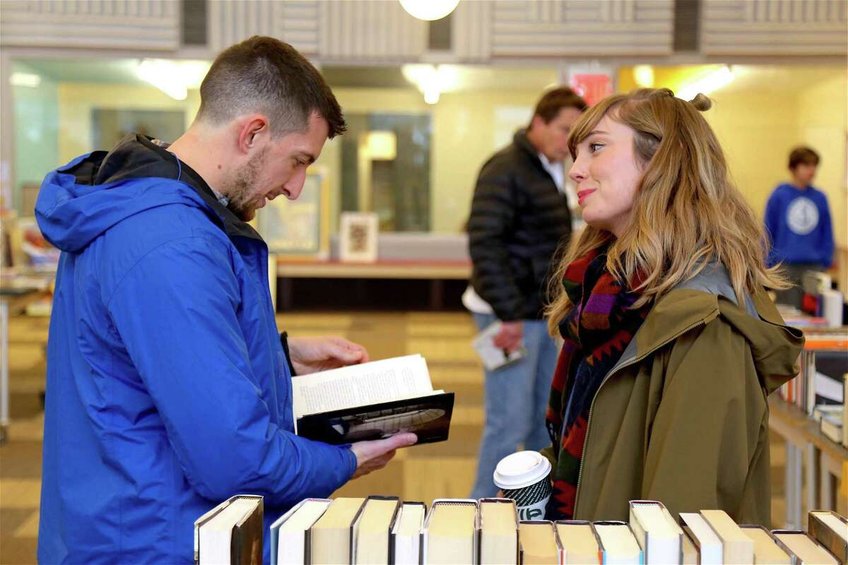 Eric Sanford of Meriden and Shannon McBride of Hamden talk about a volume at the Holiday Book Sale at The Westport Library on Nov. 24, 2019, in Westport.