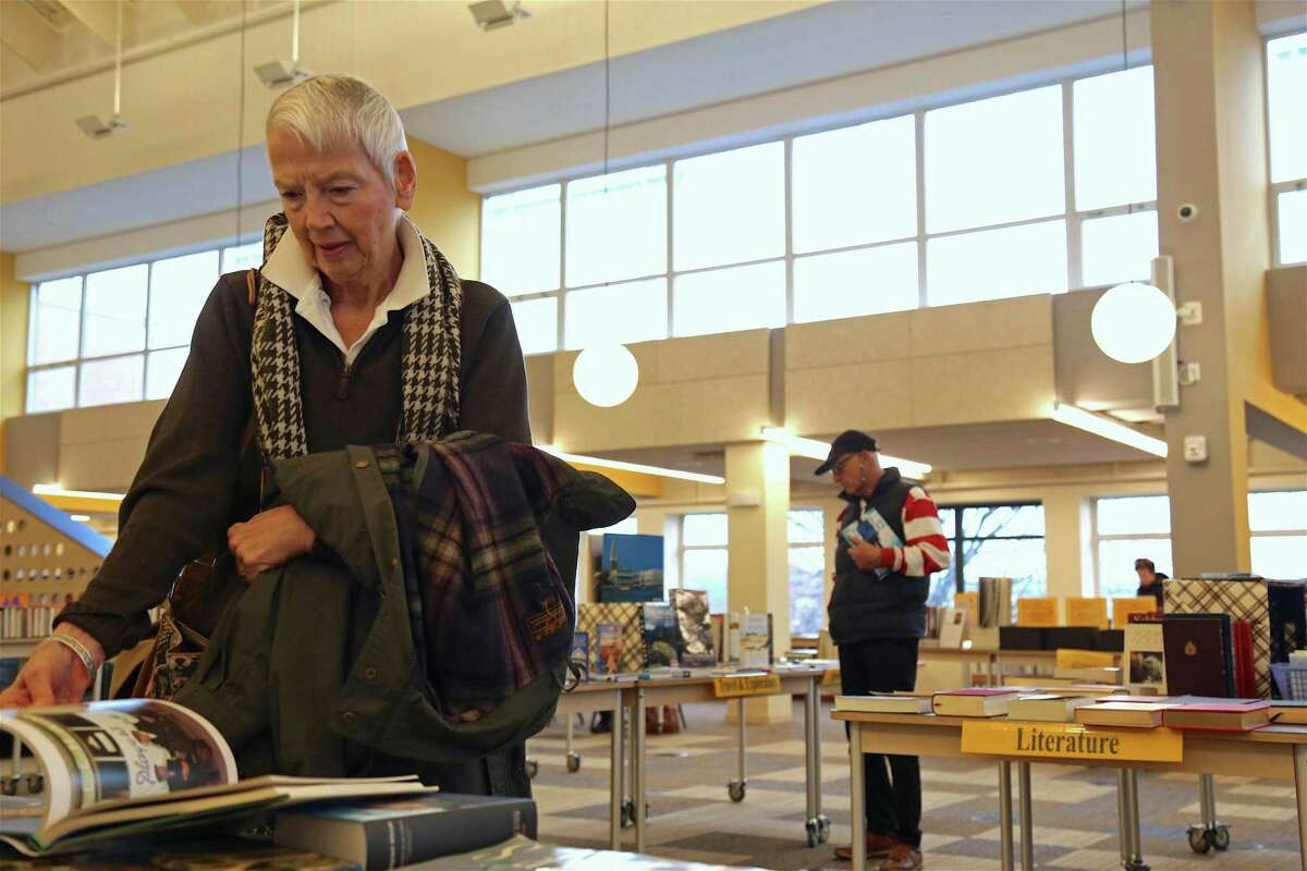 Diane Valante of Westport looks at a book at the Holiday Book Sale at The Westport Library on Nov. 24, 2019, in Westport.