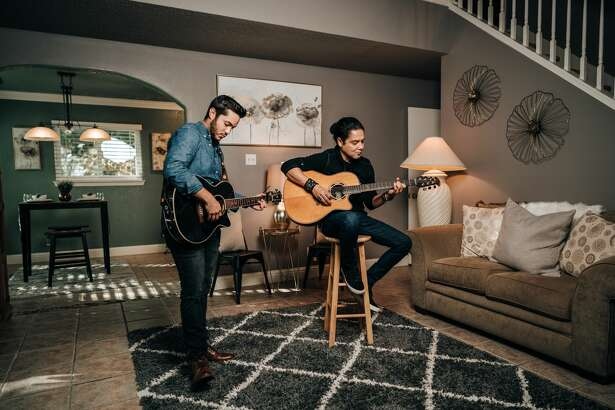 """Along with the glossy listing photos of 8479 Timber Belt showing the updated kitchen, plush backyard and spacious bedrooms, are portraits of Perez, husband of Tejano legend Selena and guitarist of """"Los Dinos,"""" playing guitar in the home with Greater San Antonio Real Estate owner and agent David Garcia Jr."""