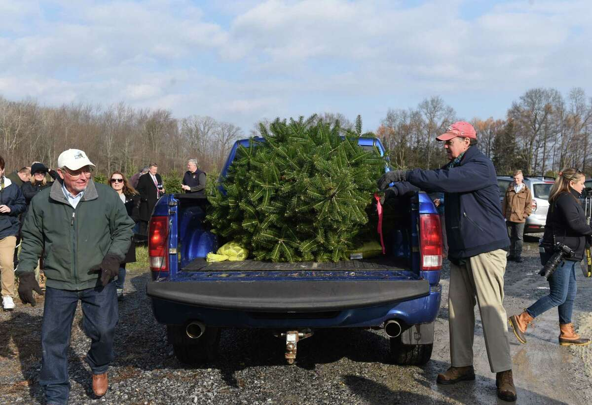 State Agriculture Commissioner Richard Ball, left, and Boulder Brook Farm owner Peter Brooks, right, load a Christmas tree to be displayed at the Adirondacks New York Welcome Center on Monday, Nov. 25, 2019, at Boulder Brook Farm in Malta, N.Y. During an event to promote the purchase of state grown Christmas trees. (Will Waldron/Times Union)