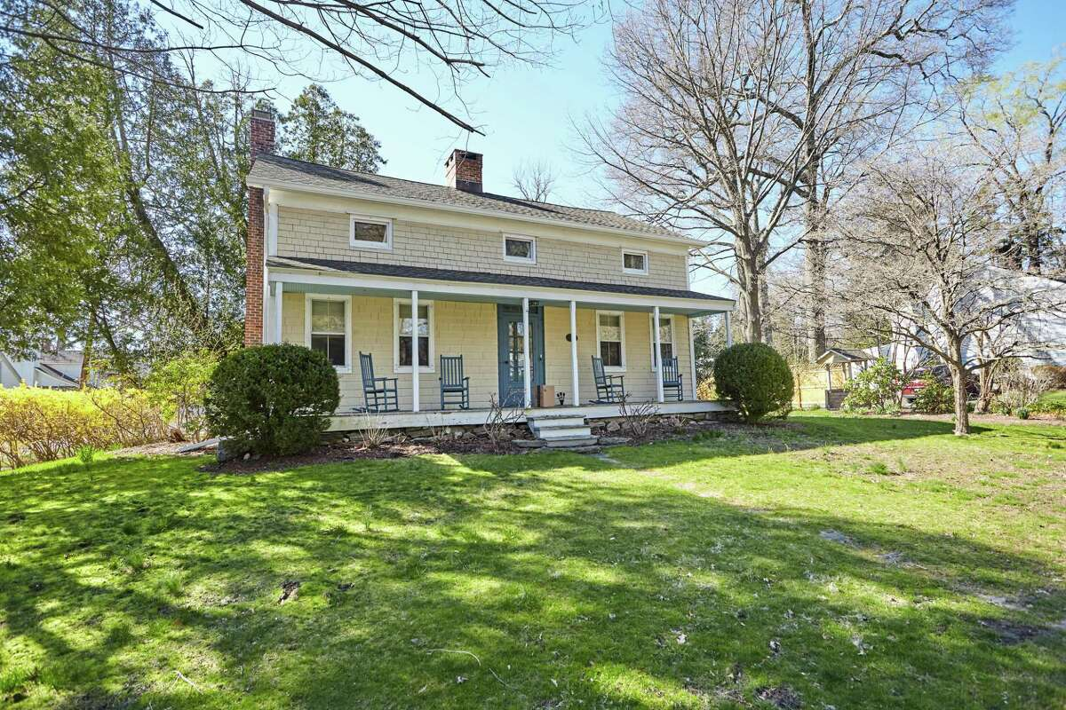 The yellow antique colonial farmhouse at 45 Kings Highway North sits on a half-acre property in the town's largest and oldest historic district.