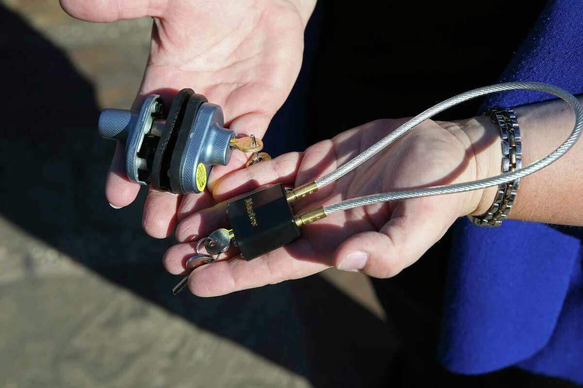 Jennifer Northway, with University Health Systems, holds gun locks during a press conference outside the Bexar County Courthouse, Monday, Nov. 25, 2019. Bexar County Judge Nelson Wolff and Sheriff Javier Salazar announced a gun safety campaign that will include public education and the distribution of thousands of gun locks.