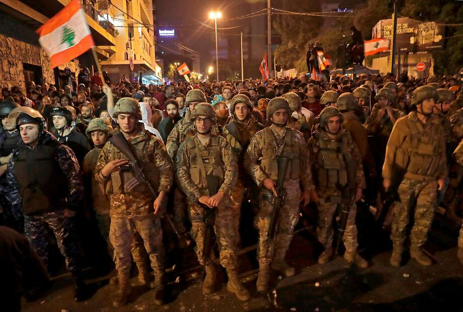 Soldiers shield anti-government protesters after brawling with backers of Hezbollah in Beirut. Photo: Anwar Amro / AFP Via Getty Images