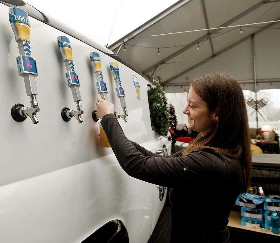 Jess Castoro, of Half-Full Brewery, pours a beer at the Winter Wonderland at Mill River Park last year. The Winter Wonderland Market & Beer Garden returns December 6 through January 1. Photo: Hearst Connecticut Media File Photo / The News-Times Freelance